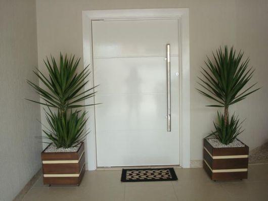 Vasos de madeira grande com planta verde, enfeitam porta de entrada branca.