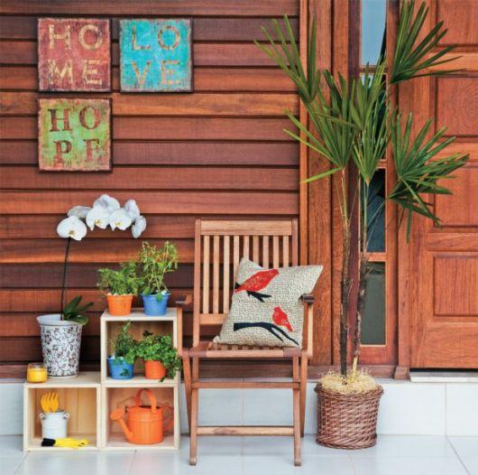 Varanda com paredes envernizadas, quadros coloridos, nichos e cadeira de madeira com vaso grande de madeira ao lado.
