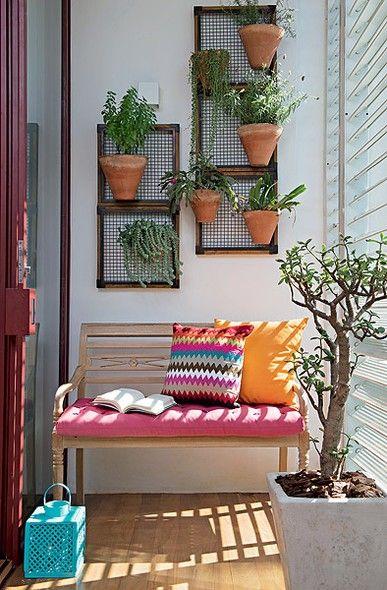 Modelo de varanda pequena com vasos de madeira para parede, sofá pequeno colorido com almofadas.