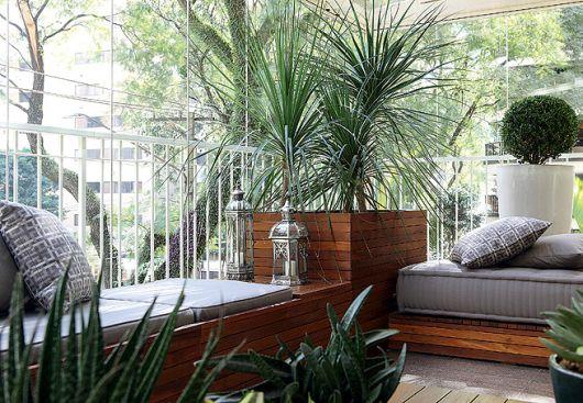 Modelo de varanda com vasos grandes de madeira com plantas grandes.
