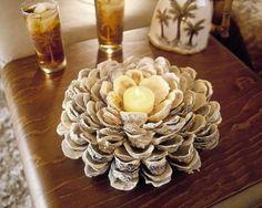 Artesanato com conchas de ostras com vela no centro.
