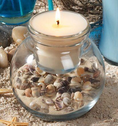 Vaso de vidro com conchas e vela no centro.