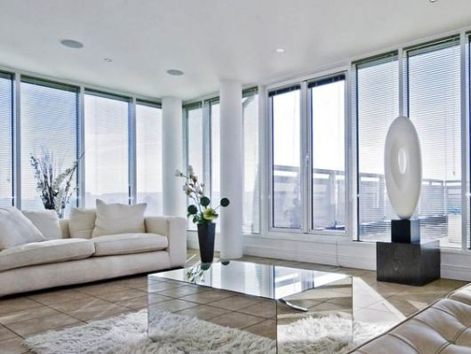 Foto de uma sala de estar com as paredes feitas a partir de grandes janelas de vidro com esquadria de PVC.