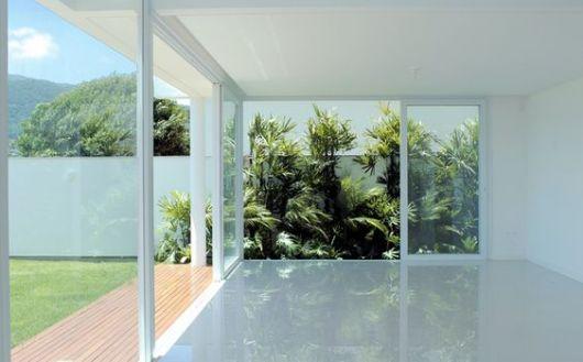 Foto de um ambiente sem decoração cujas paredes são feitas a partir de grandes janelas com esquadrias de PVC, ligando a área interna à área externa da casa.
