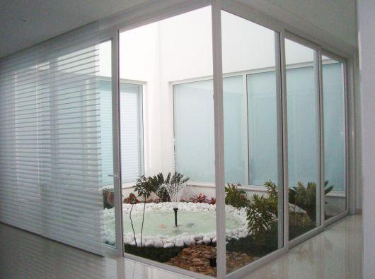 Jardim interno de uma casa cercado por grandes portas de vidro feitas com esquadria de PVC.