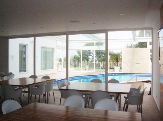 Foto de um ambiente com muitas mesas e cadeiras com portas de vidro que o conectam a uma área de piscina. As portas do ambiente são feitas com esquadria de PVC.