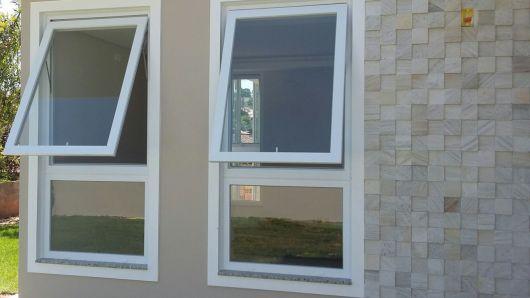 Janelas verticais que abrem para frente feitas com esquadria de PVC.