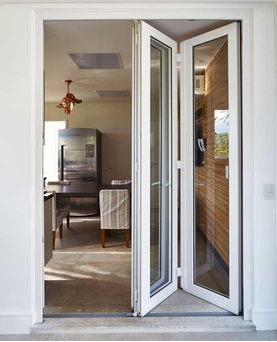 Porta com esquadria de PVC entreaberta que dá acesso a uma sala de jantar.