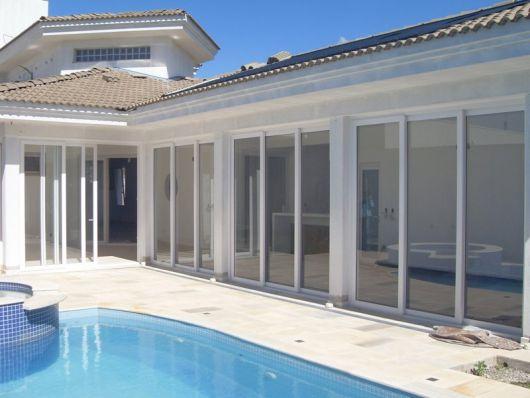 Foto de uma casa grande com piscina e muitas portas de correr em seu extensão feitas com esquadria de PVC.