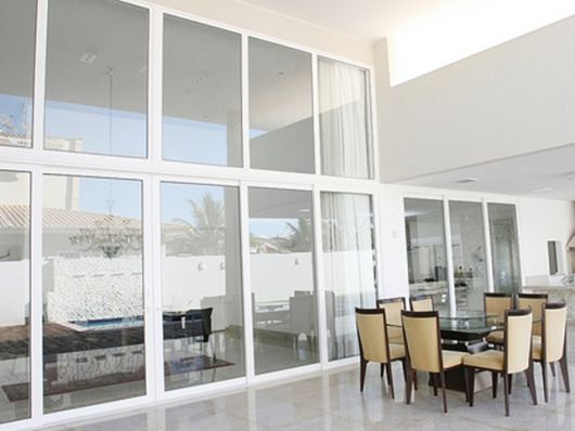 Foto de uma casa grande com muitas janelas entre seus cômodos, todas feitas com esquadria de PVC.