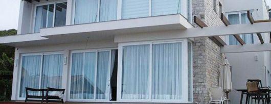 Foto tirada de uma casa cujas paredes que conectam a área externa à área interna são feitas com grandes portas de correr feitas de esquadria de PVC.