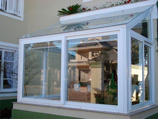 Janela de uma casa feita de vidro na parte frontal, lateral e superior com esquadria de vidro.