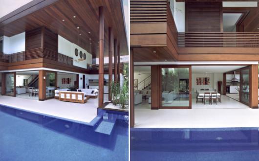 Foto de uma casa muito grande com uma porta de correr que liga a sala à piscina feita de esquadria de PVC com acabamento de madeira.