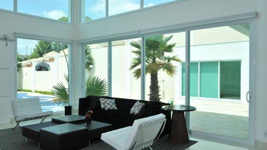 Foto de uma sala de estar com as paredes feitas a partir de grandes janelas intercaladas com esquadria de PVC.