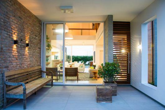 Foto tirada do quintar de uma casa, onde há uma porta de correr com esquadria de PVC que dá acesso à sala de estar.