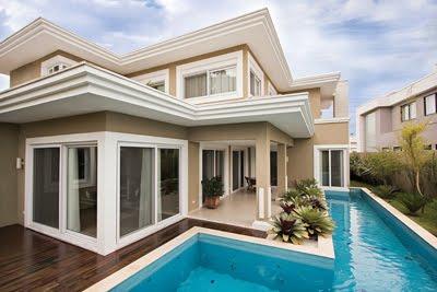 Foto de uma mansão com piscina e grandes portas de correr em praticamente todos os seus cômodos, feitas com esquadria de PVC.