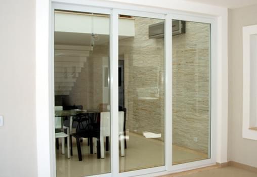 Foto de uma porta de correr com esquadria de PVC que divide dois cômodos de uma casa.