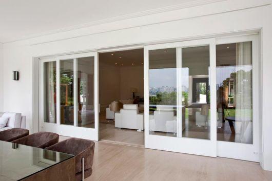 Foto de uma porta de correr bem grande feita com esquadria de PVC que divide a sala de estar e a sala de jantar.
