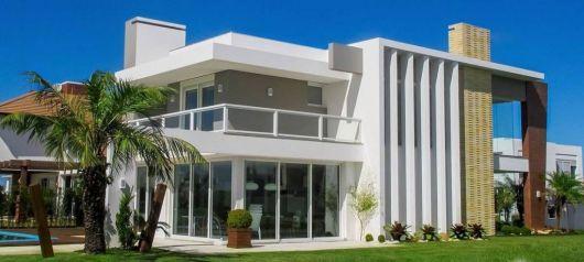 Foto de uma mansão com paredes feitas de vidro e esquadria de PVC.