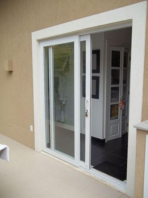 Porta de correr com esquadria de PVC que liga uma área externa a uma área interna da casa.