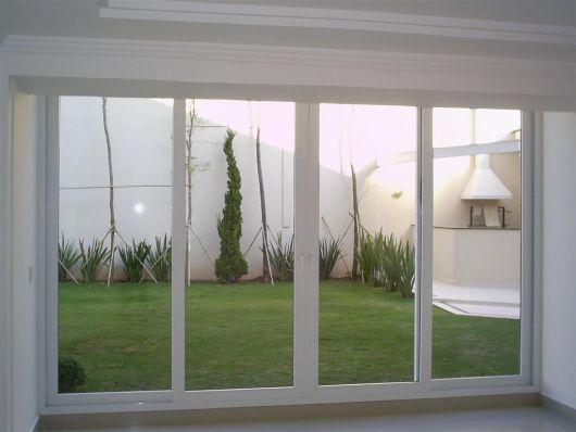 Foto tirada de dentro uma casa com portas de correr feitas de esquadria de PVC que ligam o ambiente a um quintal gramado.
