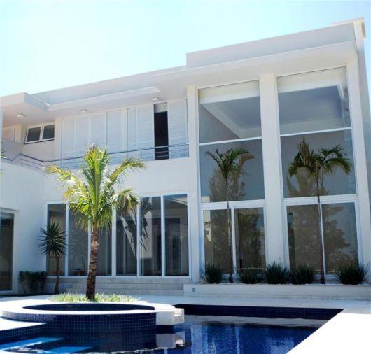 Foto de uma mansão com piscina cujas janelas e portas são muito grandes, funcionando quase como uma parede. Grande parte delas são feitas com esquadria de PVC.