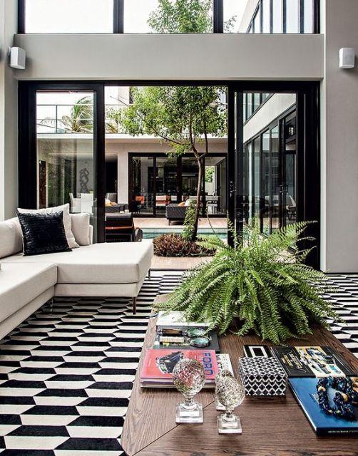 Foto tirada de dentro de uma sala de estar com portas de correr com esquadria de PVC pintada de preto.