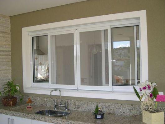 Pia da cozinha feita com uma janela acima dela. A janela é feita com esquadria de PVC simples.