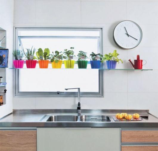 Cozinha com janela pequena e prateleira com vasos.