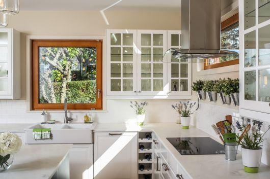 Cozinha branca com janela de madeira pequena.