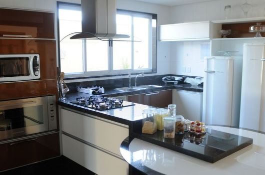 Cozinha americana com janela de vidro.