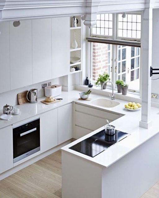 Cozinha com tons de branco e janela de vidro.