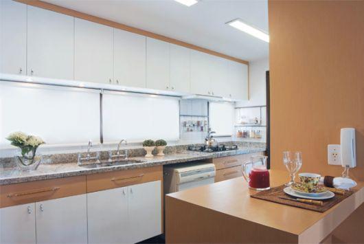 Cozinha americana em tons claros com janela.