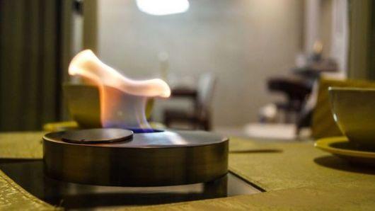 Lareira ecológica portátil com a base redonda acesa na mesa de uma cozinha.