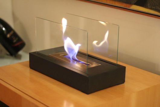 Lareira ecológica portátil com base retangular pequena acesa com sua chama protegida por vidros laterais.