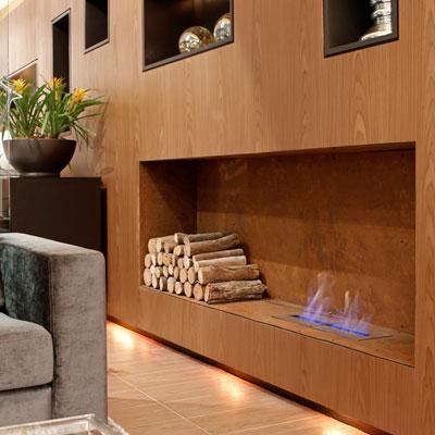 Foto de uma lareira ecológica acesa embutida em uma parede de madeira com lenhas de decoração ao seu lado.