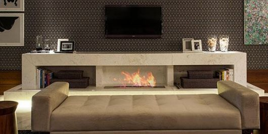 Foto de uma sala com uma lareira ecológica acesa embutida no móvel que fica em frente ao sofá e embaixo da televisão.
