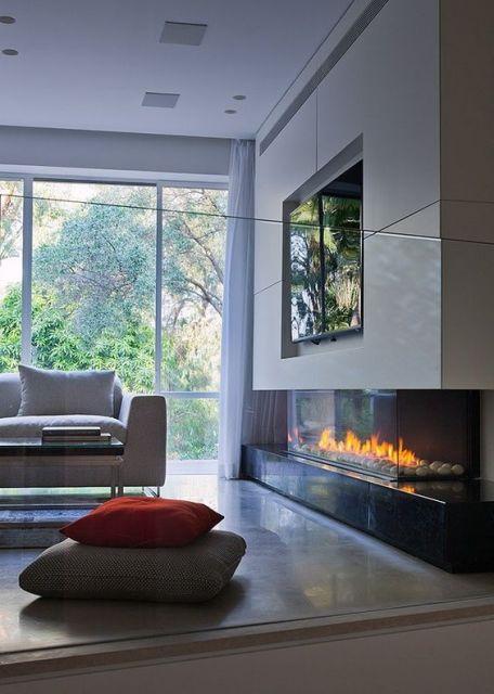 Foto de uma sala de estar com uma lareira ecológica acesa embutida em uma parede embaixo da televisão.
