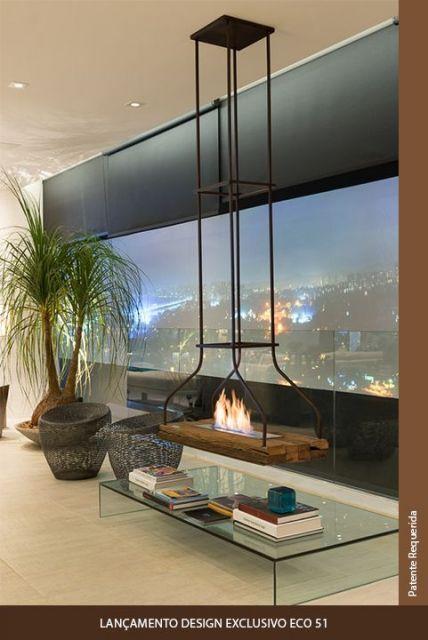 Foto de uma lareira ecológica instalada em um móvel que fica em cima da mesa de centro, cuja base de sustentação está no teto.