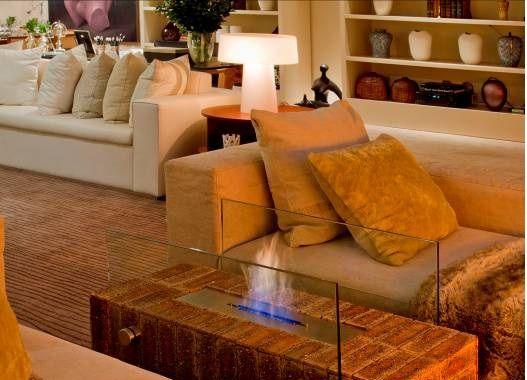 Foto de uma lareira ecológica entre dois sofás com as chamas protegidas por dois vidros laterais.