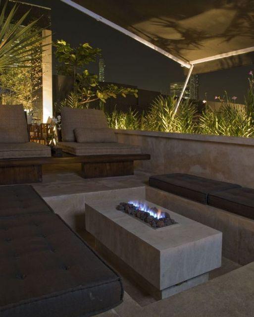 Mesa de centro com uma lareira ecológica embutida cercada por pequenas pedras em ambiente externo bastante iluminado.