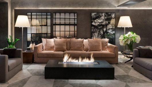 Foto de uma sala com três sofás e uma mesa de centro entre eles com uma lareira ecológica embutida acesa.