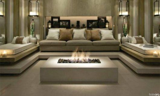 Foto de uma sala de estar bem decorada com diversos sofás e uma mesa de centro com lareira ecológica embutida.