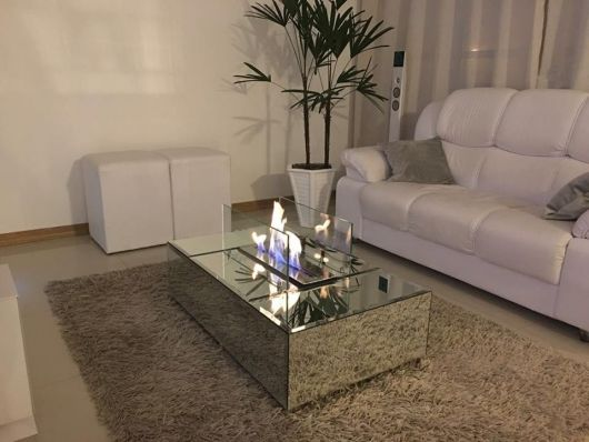 Lareira ecológica embutida em uma mesa de centro que fica em uma sala pequena com um sofá e dois pequenos bancos.