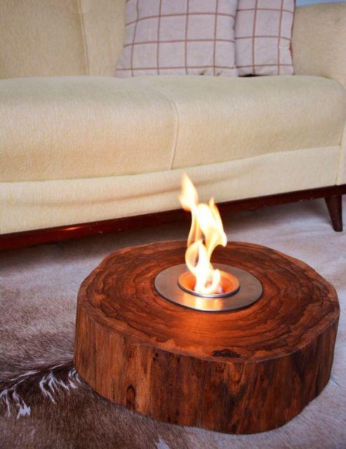 Foto com foco em um tronco de madeira redondo com uma lareira ecológica instalada em seu interior.