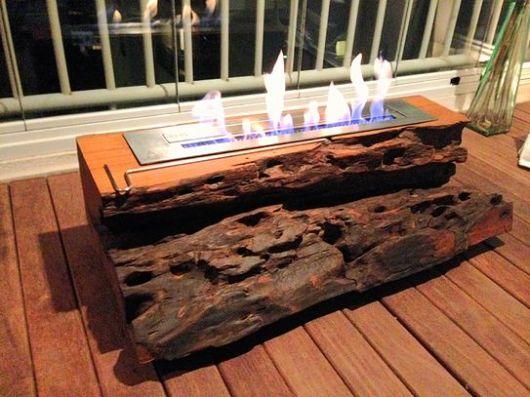 Mesa de madeira rústica com uma lareira ecológica instalada.