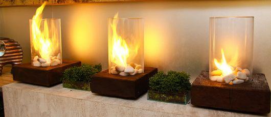 Foto de três lareiras ecológica pequenas posicionadas lado a lado, todas iguais. Elas tem uma base da madeira quadrada, chama protegida por um vidro cilíndrico e pedras em sem interior.