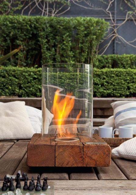 Lareira ecológica portátil com base de madeira e chama protegida por um tudo de  vidro.