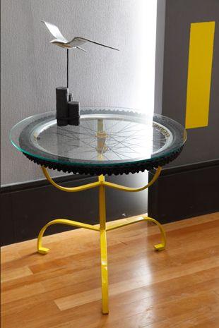 Mesa de centro com pneu de bicicleta e base amarela.