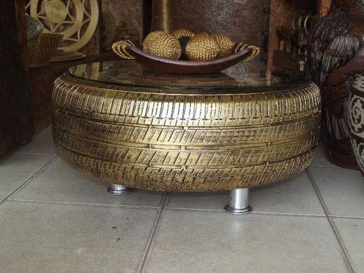 Mesa de pneu dourada com tampo de vidro.